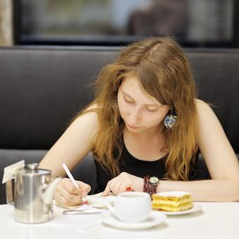 Junge frau, die in einem café arbeitet oder studiert