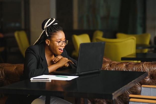 Junge frau, die in einem café sitzt, das an einem laptop arbeitet
