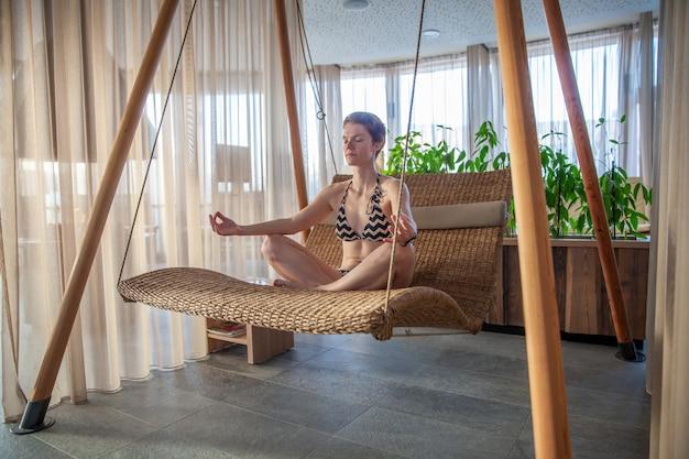 Junge frau, die in einem entspannungszentrum meditiert