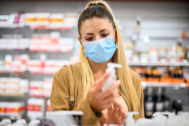 Junge frau, die in einem geschäft nach einem produkt sucht, das aufgrund von coronavirus eine maske trägt