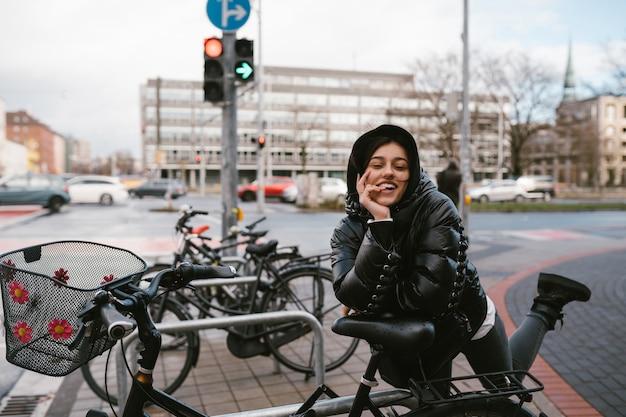 Junge frau, die in einem parkplatz mit fahrrädern aufwirft