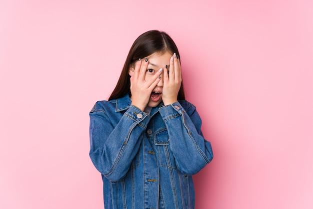 Junge frau, die in einem rosa wand-isolierten blinzeln durch erschrockene und nervöse finger aufwirft