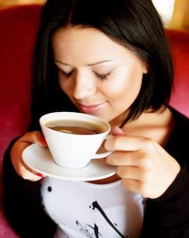 Junge frau, die in einem trinkenden kaffee des cafés sitzt
