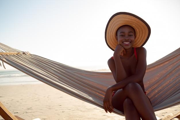 Junge frau, die in einer hängematte auf dem strand sich entspannt