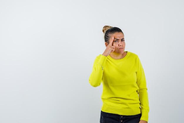 Junge frau, die in gelbem pullover und schwarzer hose den finger auf die schläfe legt und fokussiert aussieht
