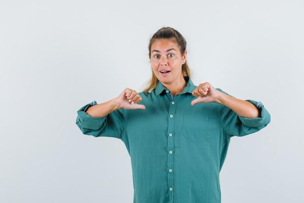 Junge frau, die in grüner bluse auf sich zeigt und glücklich schaut