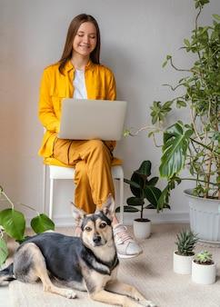 Junge frau, die in ihrem hausgarten neben ihrem hund arbeitet