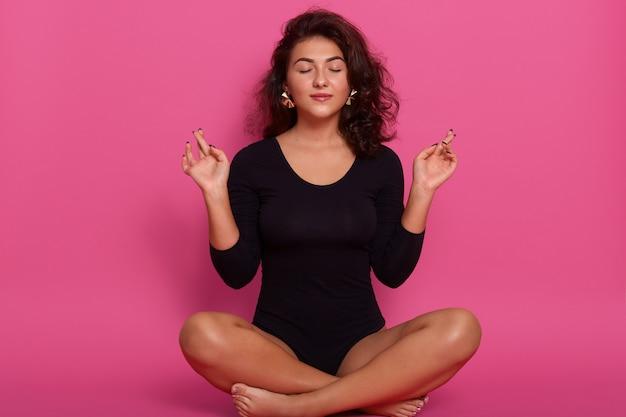 Junge frau, die in lotussitz mit geschlossenen augen sitzt, yoga macht, zu hause entspannt, schwarzes kombikleid trägt, welliges haar hat, auf dem boden auf rosa konzentrierter wand sitzt.