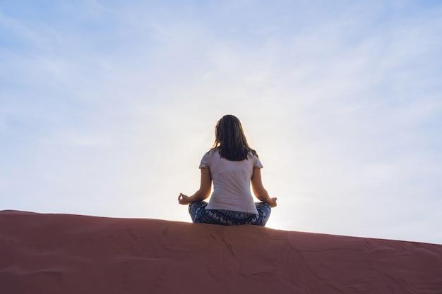 Junge frau, die in rad sandiger wüste bei sonnenuntergang meditiert