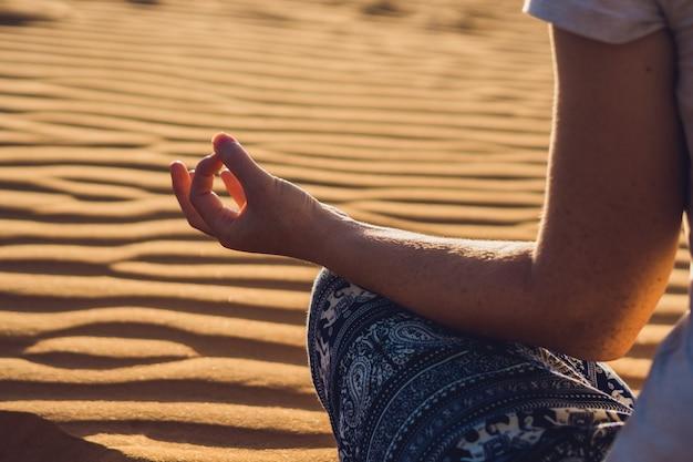 Junge frau, die in rad sandiger wüste bei sonnenuntergang oder im morgengrauen meditiert