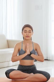 Junge frau, die in ruhe auf matte meditiert
