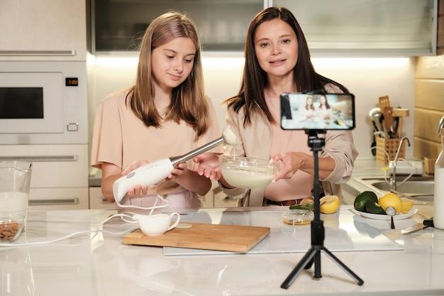 Junge frau, die in smartphone-kamera schaut und hausgemachtes eis in der küche vorbereitet, während ihr rezept mit online-publikum teilt
