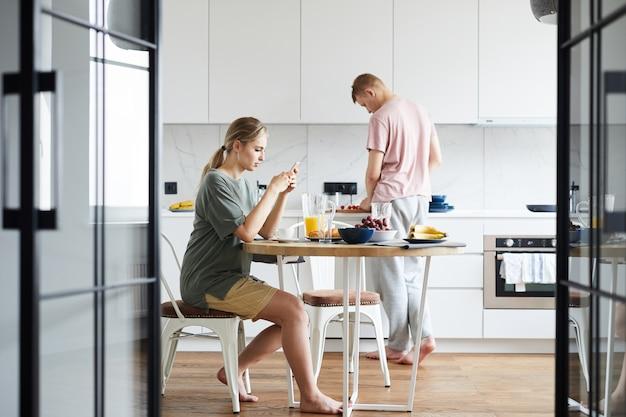 Junge frau, die in smartphone schreibt, während ihr mann kocht