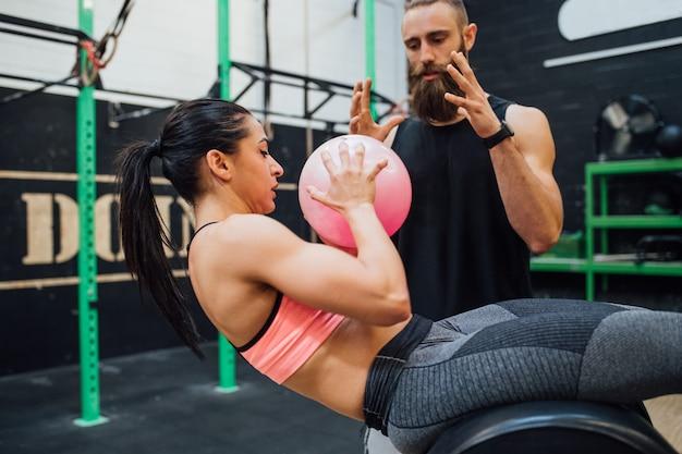 Junge frau, die innengymnastik mit persönlichem trainer ausübt