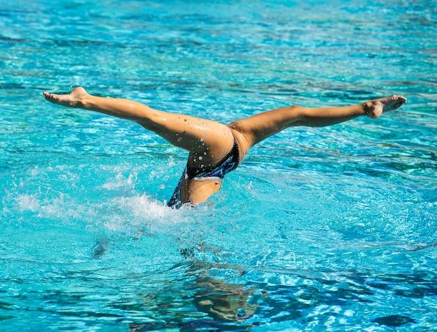 Junge frau, die innerhalb des schwimmbades aufwirft