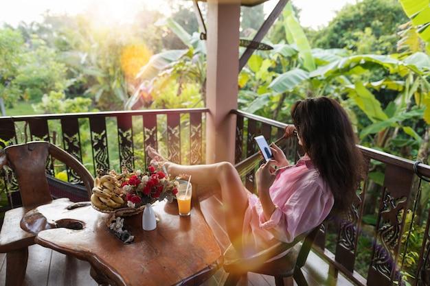Junge frau, die intelligentes telefon der zelle auf terrasse im tropischen garten hält