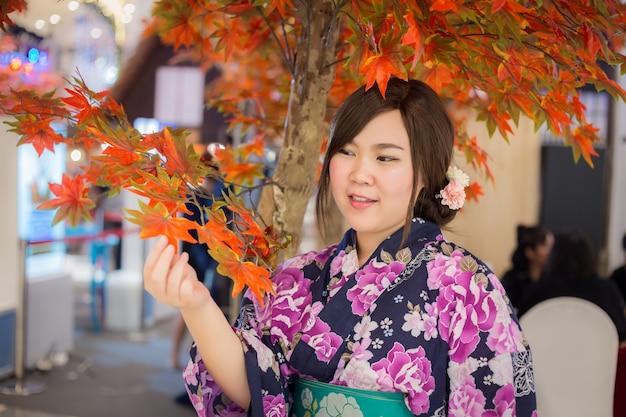 Junge frau, die japanischen traditionellen kimono in der herbstfarbe trägt. japan