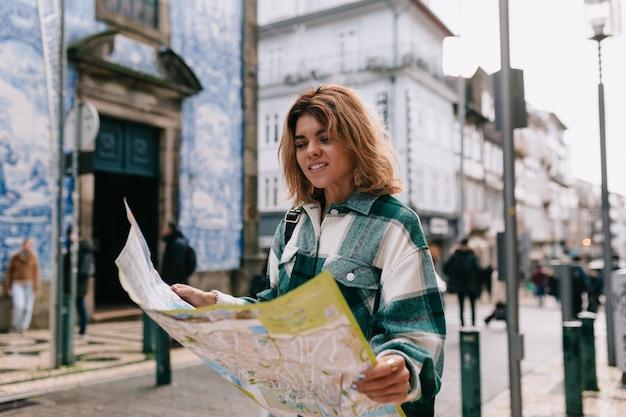 Junge frau, die jeanshemd trägt, das auf der straßenstadt mit einer karte geht