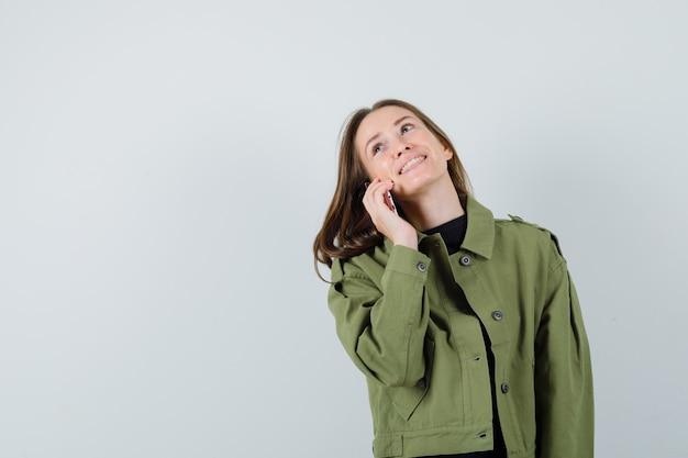 Junge frau, die jemanden über handy in grüner jacke spricht und glücklich schaut. vorderansicht. platz für text