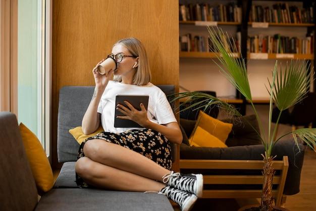 Junge frau, die kaffee an der bibliothek genießt