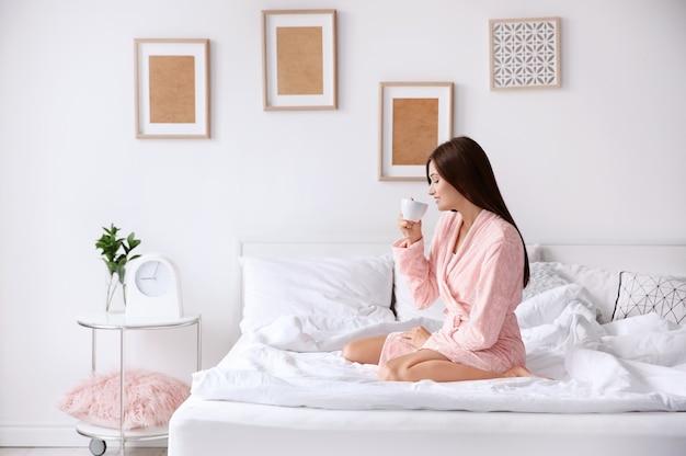 Junge frau, die kaffee beim sitzen auf bett zu hause trinkt