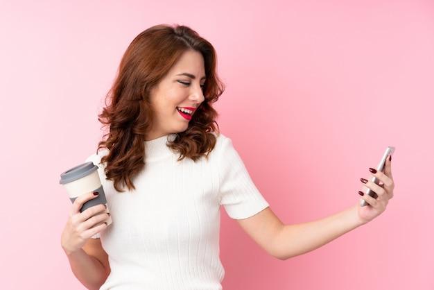 Junge frau, die kaffee hält, um und ein mobile wegzunehmen