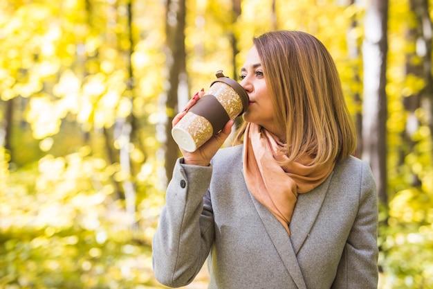 Junge frau, die kaffee im herbstpark trinkt