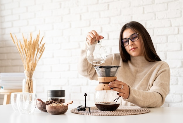 Junge frau, die kaffee im kaffeemacher braut, der heißes wasser in den filter gießt