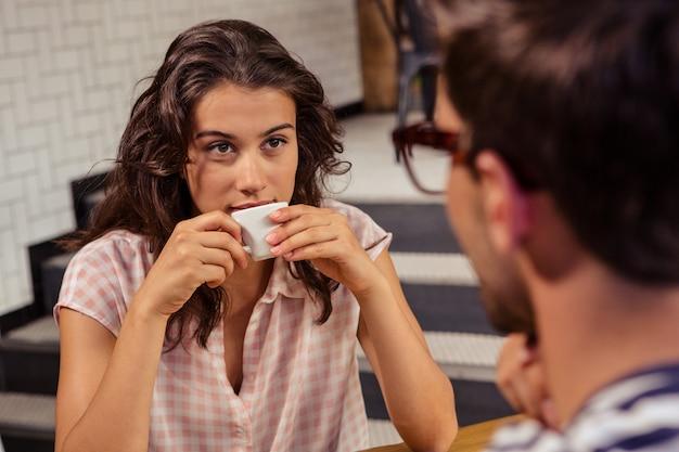 Junge frau, die kaffee in der cafeteria trinkt