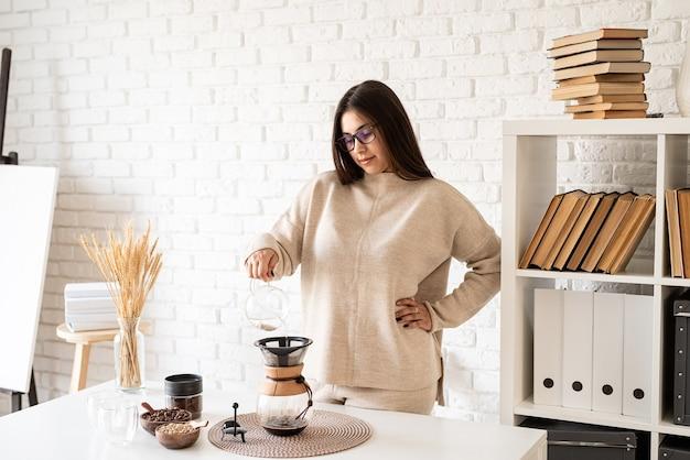 Junge frau, die kaffee in der kaffeemaschine, die am weißen tisch mit verschiedenen sachen für alternatives kaffeebrühen steht, heißes wasser in den filter gießt