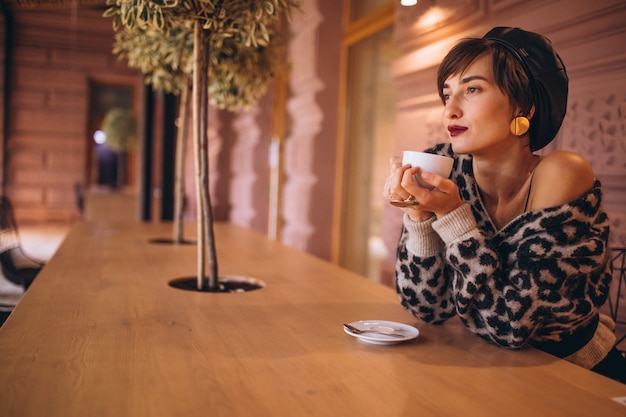Junge frau, die kaffee in einem café trinkt
