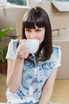 Junge frau, die kaffee in ihrem neuen haus trinkt