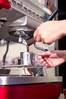 Junge frau, die kaffee macht