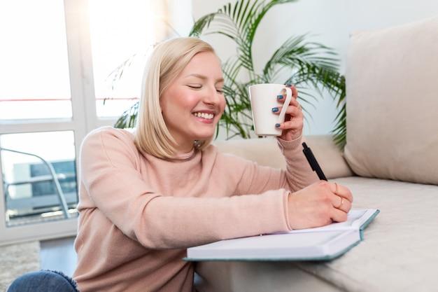 Junge frau, die kaffee studiert und trinkt, fleißige junge frau, die zu hause arbeitet und auf dem boden im wohnzimmer mit einer klasse notizen in ordnern sitzt, die für universität studieren