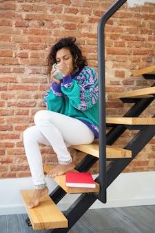 Junge frau, die kaffee trinkt. sie sitzt auf der treppe ihres hauses neben einem buch.