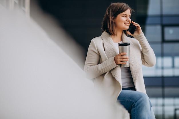 Junge frau, die kaffee trinkt und telefon außerhalb der straße benutzt