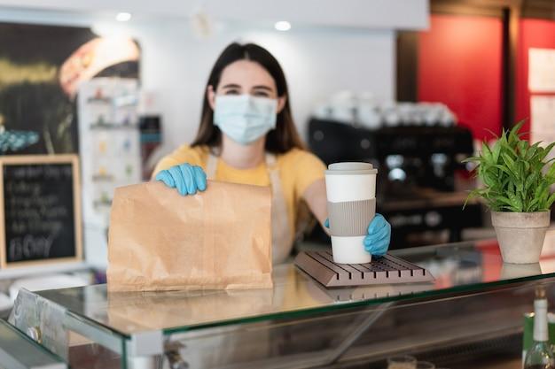 Junge frau, die kaffee zum mitnehmen und frühstück am kaffeehaus beim tragen der schutzgesichtsmaske dient