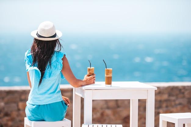 Junge frau, die kalten kaffee genießt, der meerblick im straßencafé genießt