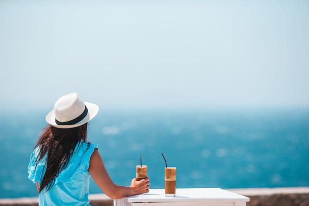 Junge frau, die kalten kaffee trinkt, der meerblick genießt. schöne frau entspannen während des exotischen urlaubs am strand, der frappe genießt