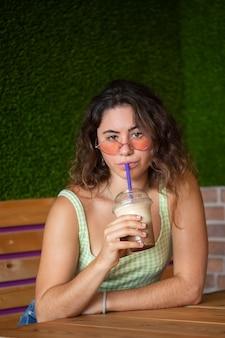Junge frau, die kamera beim trinken eines smoothie betrachtet.