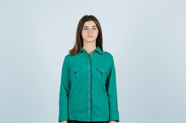 Junge frau, die kamera im grünen hemd betrachtet und hoffnungsvoll schaut. vorderansicht.