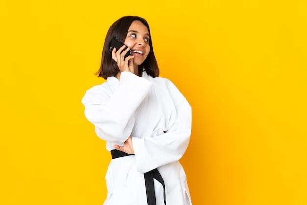 Junge frau, die karate lokalisiert auf gelber wand hält kaffee hält, um und ein handy wegzunehmen