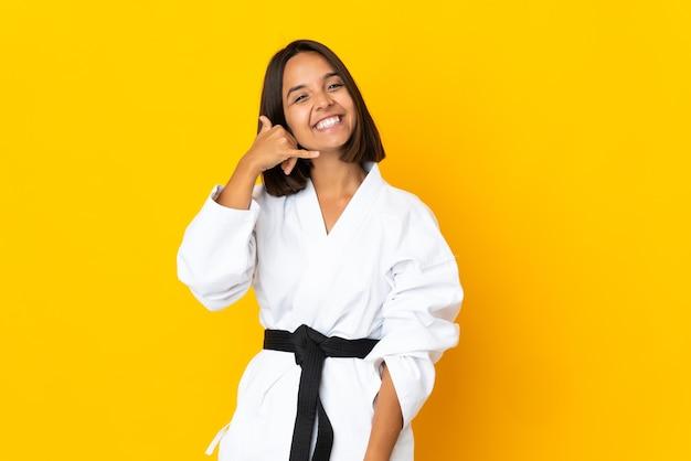 Junge frau, die karate lokalisiert auf gelber wand macht, die telefongeste macht. rufen sie mich zurück zeichen