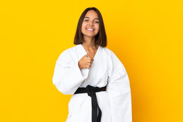 Junge frau, die karate lokalisiert auf gelber wand tut, die eine daumen hoch geste gibt