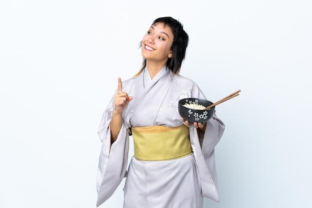 Junge frau, die kimono trägt, der eine schüssel nudeln über weißer wand hält, die beabsichtigt, die lösung zu realisieren, während ein finger anhebt