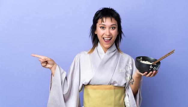 Junge frau, die kimono über isoliertem blauem hintergrund trägt, überrascht und zeigt finger zur seite, während eine schüssel nudeln mit essstäbchen hält