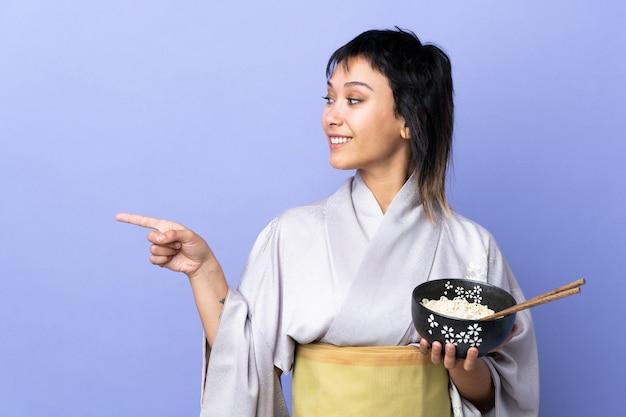 Junge frau, die kimono über isolierter blauer wand trägt, die zur seite zeigt, um ein produkt zu präsentieren, während eine schüssel nudeln mit stäbchen hält