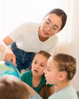 Junge frau, die kindern geographie lehrt
