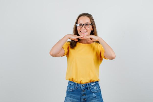Junge frau, die kinn auf händen stützt und im t-shirt, in den shorts, in der vorderansicht der brille lächelt.