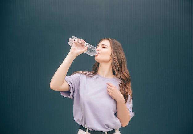 Junge frau, die klares leckeres wasser aus transparenter plastikflasche trinkt